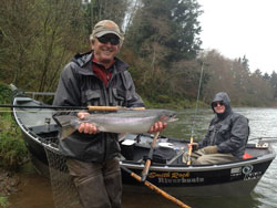 A client with a steelhead caught on a river on the Oregon Coast